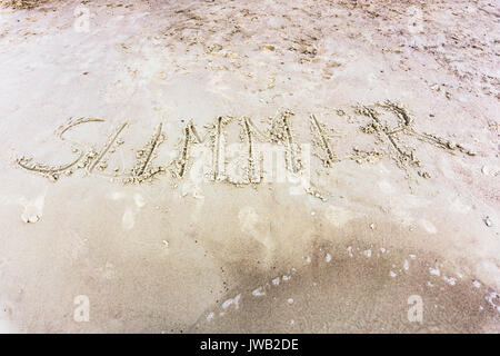 Summer written in the sand on a sunset beach. Vacation and holiday theme - Stock Photo