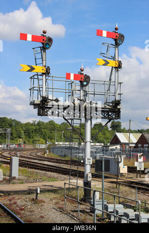 Set of semaphore signals on a gantry at one end of Worcester Shrub Hill railway station seen against a mainly blue - Stock Photo