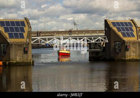 Pedestrians cross the River Lagan on the footbridge across the flood defense barrier in Belfast,Northern Ireland - Stock Photo