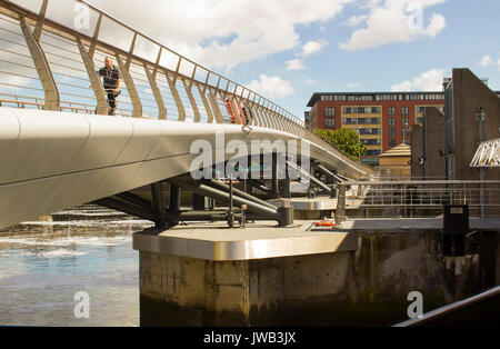 A cyclist crosses the new footbridge across the new flood barrier on the River Lagan at the Donegall Quay in the - Stock Photo