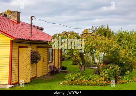 Yellow wooden house with tree and cosy green yard - Stock Photo