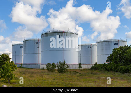 Silver oil tanks on the green grass field. Blue sky with clouds. - Stock Photo
