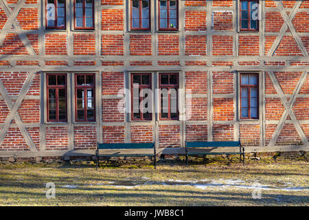 Brick wall texture background on day noon light with windows and benhes. Northen fort style. - Stock Photo