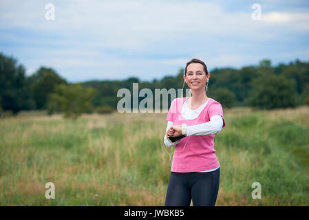 A healthy, smiling woman in fit wear with smart phone, watch and earphones, exercising outdoors in nature. - Stock Photo