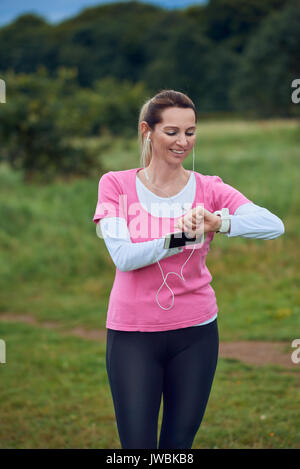 Middle-aged woman checking her sport or health watch while out jogging in the countryside listening to music on - Stock Photo