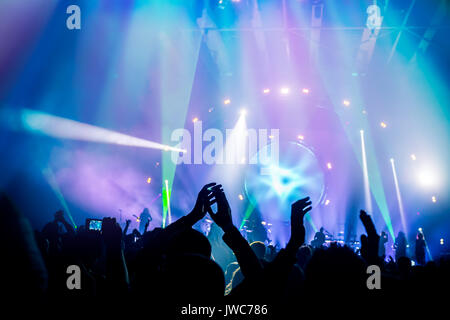 Many people enjoying concert, band performs on stage in the bright blue light, people enjoying music, dancing with - Stock Photo