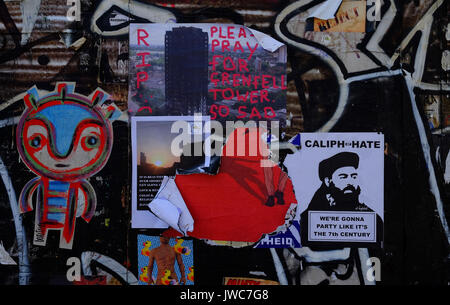 A poster expressing sadness for the victims of Grenfell Tower amongst the graffiti on a wall in Brick Lane, in London's - Stock Photo