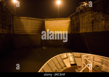 A cruise boat is tied to guiding train engines as the vessel enters Gatun Locks from the Atlantic entrance of the - Stock Photo