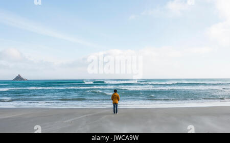 Lonely person standing by the sea, looking out into the distance, Sandfly Bay, Dunedin, Otago, South Island, New - Stock Photo