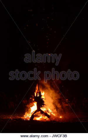 A costumed person in silhouette in front of a fire during a Baining fire dance. - Stock Photo