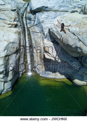 A woman jumps into a pool of water off of a cliff. - Stock Photo