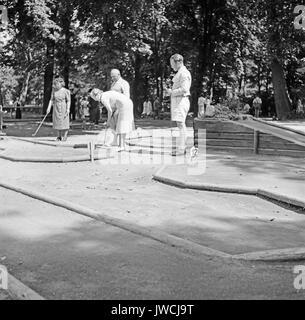 People playing miniature golf. - Stock Photo