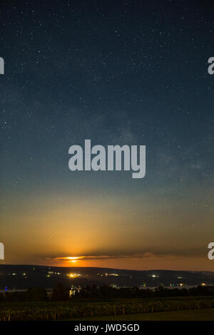 Moon rising over vinyard and lake under stars and milky way - Stock Photo