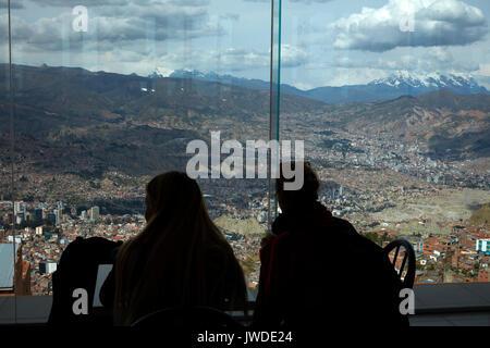 Tourists & view of La Paz and Illimani (6438m/21,122ft), from top of teleferico at Estacion Teleferico Parque Mirador, - Stock Photo