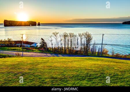 Famous Rocher Perce rock in Gaspe Peninsula, Quebec, Canada, Gaspesie region with cityscape at sunrise and sun - Stock Photo