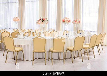 Beautifully decorated room in pastel shades of white with covered tables with flowers in the restaurant for the - Stock Photo