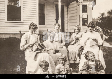 Women sewing needlepoint with small children outdoors in Minnesota USA 1907-1908 having fun - Stock Photo