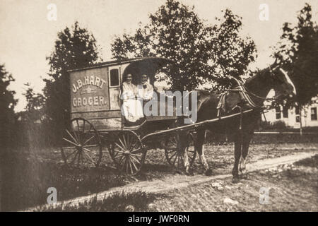 Two Women in a JB Hart Grocer delivery wagon in Minnesota USA 1907-1908 and having fun - Stock Photo