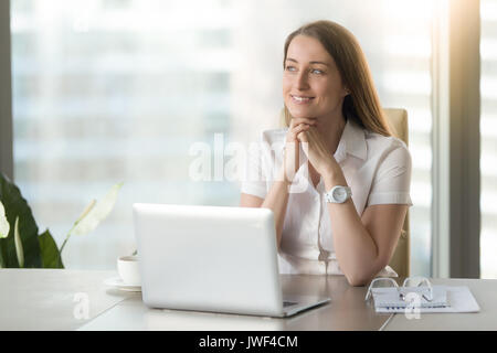 Meditative smiling businesswoman dreaming of future success at w - Stock Photo