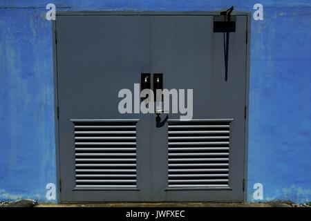 Photo of a gray steel door and a blue concrete wall - Stock Photo