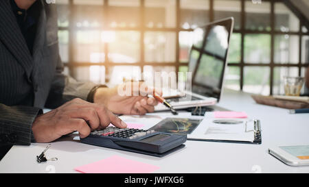 Business man calculating finance on calculator in a office 16:9 size. - Stock Photo