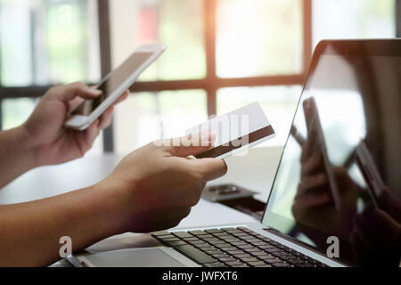 Man paying with credit card on smart phone at home office buy online e-commerce concept. - Stock Photo