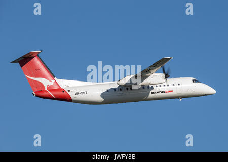 QantasLink (Qantas) deHavilland DHC-8 (Dash 8) twin engined regional airliner aircraft departing Sydney Airport. - Stock Photo