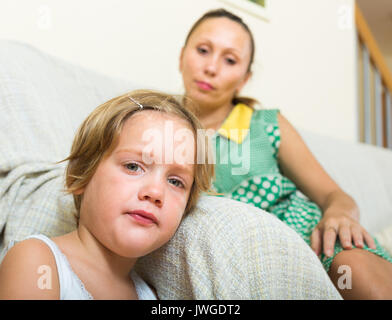 Little daughter and unpleased mother sitting on couch at home - Stock Photo