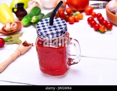 Freshly made juice from a ripe red tomato in a glass jar with a straw on a white wooden background - Stock Photo