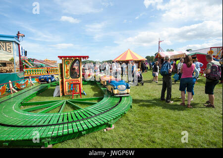 Families enjoying a day out in the sunshine at a children's funfair at Vintage steam rally, UK GB England - Stock Photo