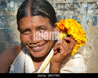 Closeup street portrait (outdoor headshot, seven-eighths view) of a smiling mature Indian Adivasi flower seller - Stock Photo