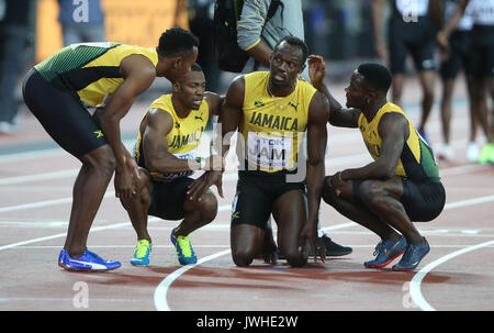London, UK. 12th Aug, 2017. Usain Bolt Is Helped Over The Line 4 X100 Metres World Athletics Championships 2017 - Stock Photo