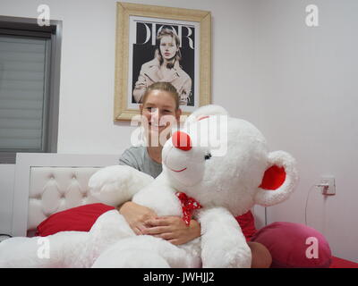 Tel Aviv, Israel. 10th July, 2017. Israeli model Sofia Mechetner cuddling with her stuffed bear Pinky in the house - Stock Photo