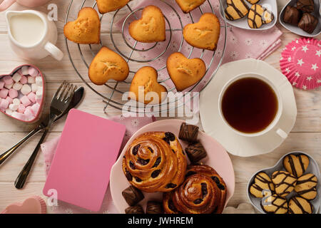 Flat lay cakes and cookies, muffins and rolls, biscuits and sweets, tea and coffee with marshmallow. Top view. - Stock Photo