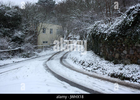 British Channel Islands. Alderney. Winter scene of cottage and snow-covered country lane. - Stock Photo