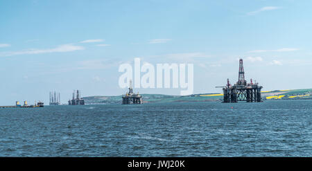 Panorama of a row of decommissioned oil rigs from the North Sea in the Cromarty Firth, Scotland