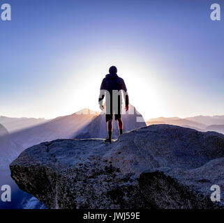 Glacier Point and view of Half Dome with person looking off silhouette. Sunrise views from Glacier Point up to the - Stock Photo