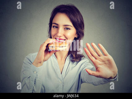 Happy woman says no to diet restrictions enjoying her cheeseburger - Stock Photo