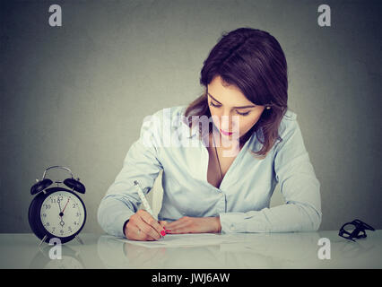 Serious business woman writing a letter or filling out an application form - Stock Photo