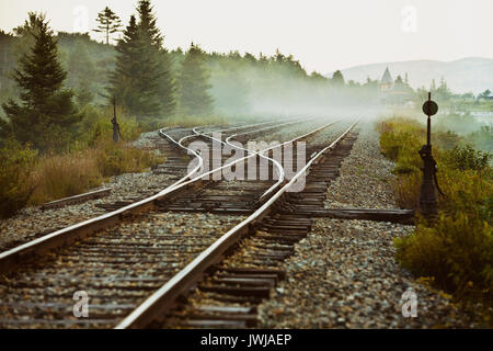 The fog shrouded rails of the Conway Scenic Railroad's Notch Train at the Crawford Station. - Stock Photo