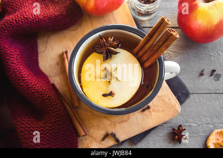Hot drink of apple tea with cinnamon stick, star anise and clove. Seasonal mulled wine in mug on wooden background. - Stock Photo