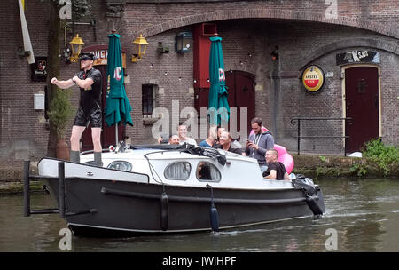 A boat carrying a stag party sails on a canal in Utrecht, the Netherlands, August 5, 2017. © John Voos - Stock Photo