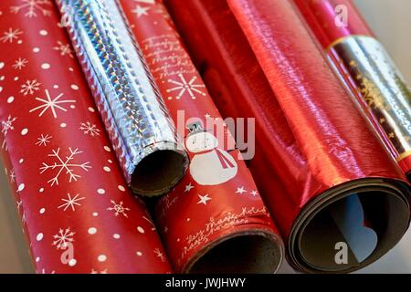 Close up of rolls of red and silver Christmas wrapping paper - Stock Photo