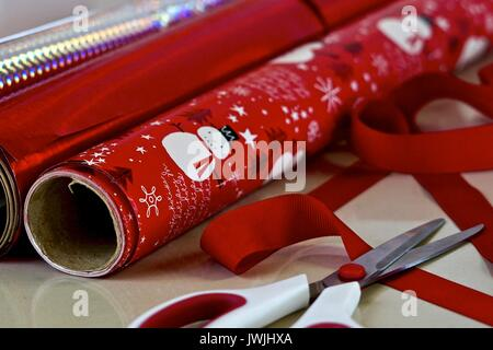 Rolls of Christmas wrapping paper and scissors - Stock Photo