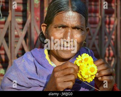 Closeup street portrait (outdoor half-length portrait, seven-eighths view) of an elderly Indian Adivasi market woman - Stock Photo