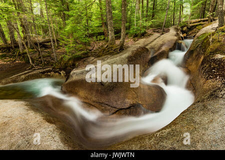 A chute/slide cuts through hard granite along the Pemigewasset River in spring, Grafton Co., Franconia Notch State - Stock Photo
