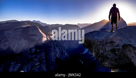 Glacier Point and view of Half Dome with person on the edge. Sunrise views from Glacier Point up to the very edge - Stock Photo