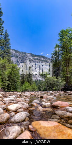 Stream in Yosemite with rocky shallows. Water ways in Yosemite with the forest surrounding - Stock Photo