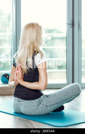 Young woman practicing yoga in the gym. girl joining hands behind her back - Stock Photo