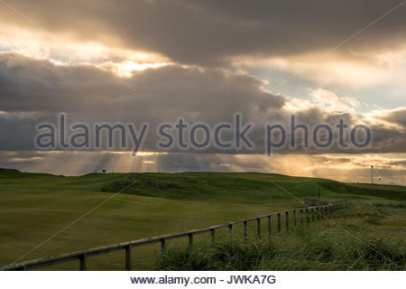 View of sun setting behind clouds with sunburst across putting green, North Berwick, East Lothian, Scotland, UK. - Stock Photo